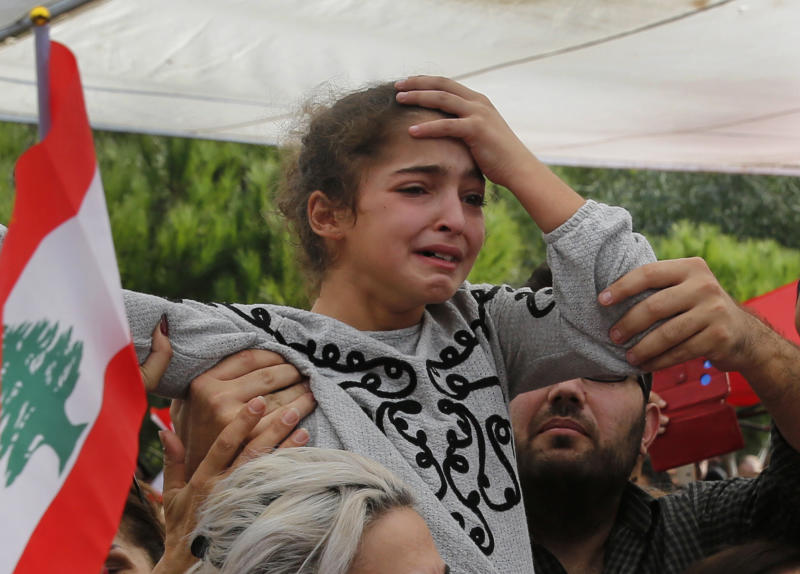 The daughter of of Alaa Abu Fakher, who was killed by a Lebanese soldier in Tuesday night protests south of Beirut, mourns during her father's funeral, in Choueifat neighborhood, Lebanon, Thursday, Nov. 14, 2019. For nearly a month, the popular protests engulfing Lebanon have been startlingly peaceful. But the shooting death of Fakher, a 38-year-old father by a soldier, the first such fatality in the unrest, points to the dangerous, dark turn the country could be heading into.. (AP Photo/Hussein Malla)