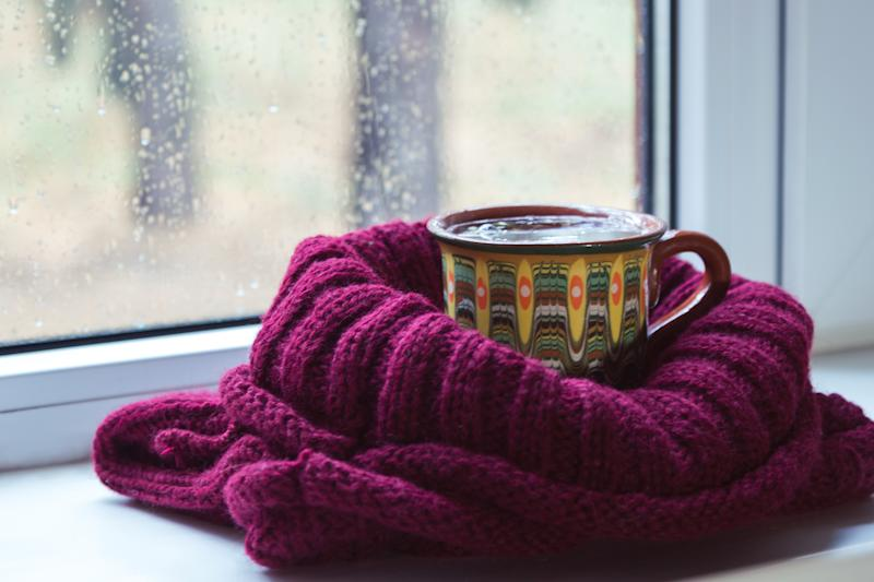 A cup of tea wrapped in a knit scarf is on the window sill.