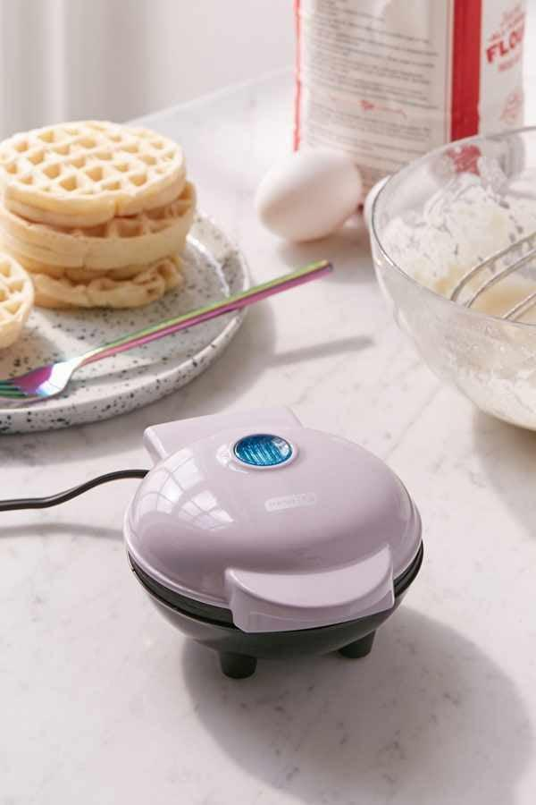 """<p>Sunday brunch at you and your roomie's apartment just got so much cuter! This <a href=""""https://www.popsugar.com/buy/Mini-Waffle-Maker-335630?p_name=Mini%20Waffle%20Maker&retailer=urbanoutfitters.com&pid=335630&price=18&evar1=savvy%3Aus&evar9=32491647&evar98=https%3A%2F%2Fwww.popsugar.com%2Fsmart-living%2Fphoto-gallery%2F32491647%2Fimage%2F45416904%2FMini-Waffle-Maker&list1=shopping%2Cfood%2Cgifts%2Choliday%2Cgift%20guide%2Cedible%20gifts%2Cinstagram%2Cbudget%20tips%2Choliday%20living%2Cgifts%20for%20women%2Cgifts%20under%20%24100%2Cgifts%20under%20%2450%2Cgifts%20under%20%2475&prop13=mobile&pdata=1"""" rel=""""nofollow"""" data-shoppable-link=""""1"""" target=""""_blank"""" class=""""ga-track"""" data-ga-category=""""Related"""" data-ga-label=""""https://www.urbanoutfitters.com/shop/mini-waffle-maker-001"""" data-ga-action=""""In-Line Links"""">Mini Waffle Maker</a> ($18) is perfect for anyone who loves making breakfast for every occasion.</p>"""