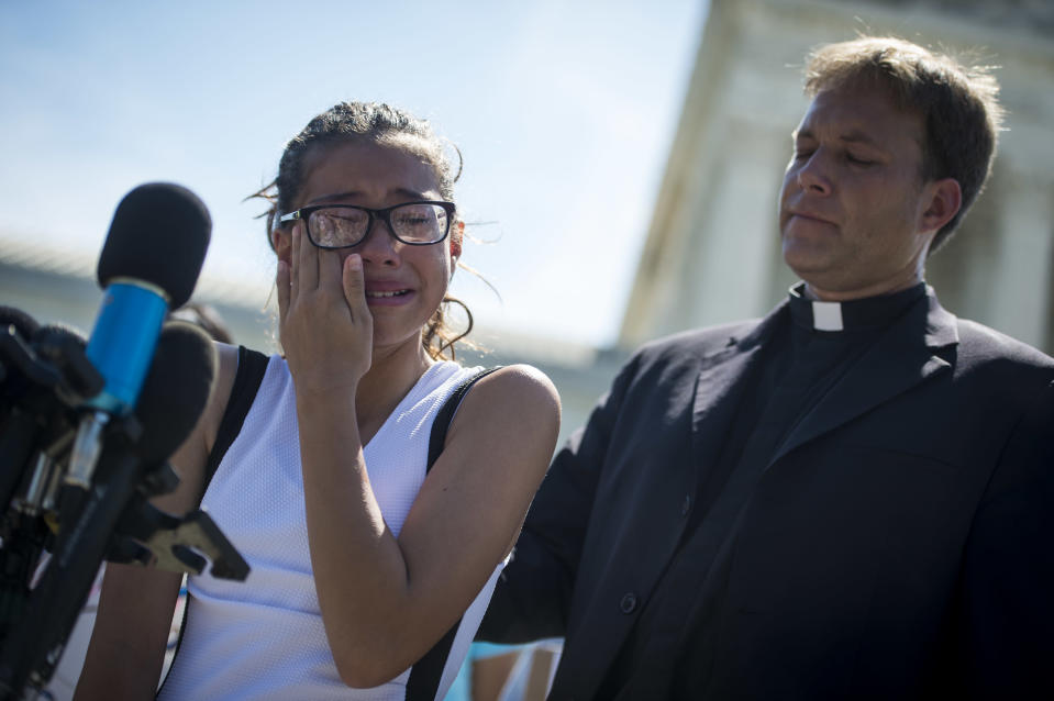 <p>A girl cries as she speaks to the press outside the Supreme Court about her father who was detained by ICE agents after they released a decision about the travel ban Tuesday June 26, 2018. (Photo: Sarah Silbiger/CQ Roll Call/Getty Images) </p>