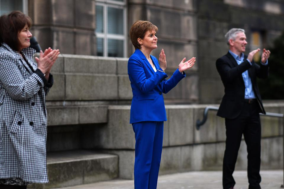 "Scotland's First Minister Nicola Sturgeon takes part in a national ""clap for carers"" to show thanks for the work of Britain's National Health Service (NHS)workers and frontline medical staff around the country as they battle with the novel coronavirus pandemic, outside St Andrew's House in Edinburgh on April 16, 2020. - Britain on Thursday extended its lockdown to tackle the coronavirus for ""at least the next three weeks"", as it remains among the countries worst-hit by the pandemic with hundreds dying daily from the disease. (Photo by Jeff J Mitchell / POOL / AFP) (Photo by JEFF J MITCHELL/POOL/AFP via Getty Images)"