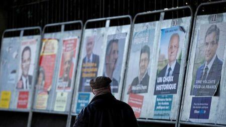 A man looks at campaign posters of the 11th candidates who run in the 2017 French presidential election in Enghien-les-Bains, near Paris, France April 19, 2017.   REUTERS/Christian Hartmann - RTS12ZQ5