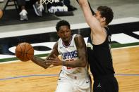 LA Clippers' Lou Williams looks to pass around Milwaukee Bucks' Brook Lopez during the first half of an NBA basketball game Sunday, Feb. 28, 2021, in Milwaukee. (AP Photo/Morry Gash)