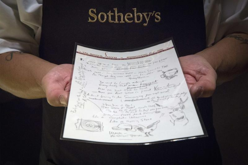 """A Sotheby's employee shows the handwritten lyrics for Bob Dylan's 'Like a Rolling Stone' song that is part part of a collection from; 'A Rock and Roll History: Presley to Punk' at Sotheby's auction house in New York, June 20, 2014. Bob Dylan's lyrics for """"Like a Rolling Stone"""" and """"A Hard Rain's A-Gonna Fall"""" are expected to be the highlights of Sotheby's rock and roll auction next week, which will include memorabilia from the Beatles, the Rolling Stones and Elvis Presley. REUTERS/Brendan McDermid (UNITED STATES - Tags: ENTERTAINMENT BUSINESS SOCIETY)"""