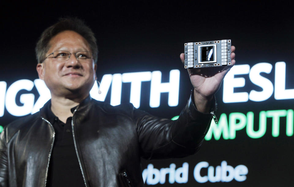 NVIDIA CEO Jen-Hsun Huang shows NEW HGX with TESLA V100 VERSA GPU CLOUD COMPUTING as he talks about AI and gaming during the Computex Taipei exhibition at the world trade center in Taipei, Taiwan, Tuesday, May 30, 2017. (AP Photo/Chiang Ying-ying)