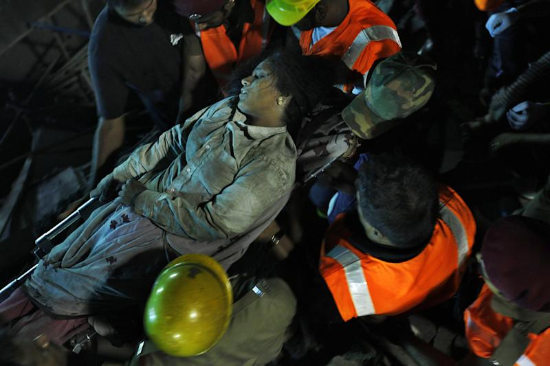 Rescuers carry an injured woman worker  pulled out from the rubble of a building that collapsed on the outskirts of Chennai, India, Sunday, June 29, 2014. The 12-story apartment structure the workers were building collapsed late Saturday while heavy rains and lightning were pounding. Police said 31 construction workers had been pulled out so far and the search was continuing for more than a dozen others. (AP Photo/Arun Sankar K)