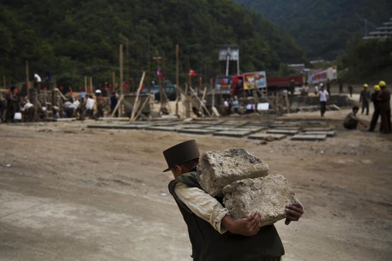"""In this Friday Sept. 20, 2013 photo, a North Korean construction worker carries bricks at a building project to construct a ski resort at North Korea's Masik Pass. North Korean authorities have been encouraging a broader interest in sports and recreation in the country, calling it """"the hot wind of sports blowing through Korea."""" (AP Photo/David Guttenfelder)"""