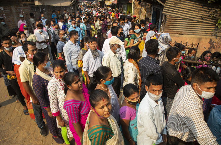 People stand in queue to cast their votes in a polling station during the third phase of assembly election in Gauhati, India, Tuesday, April 6, 2021. (AP Photo/Anupam Nath)