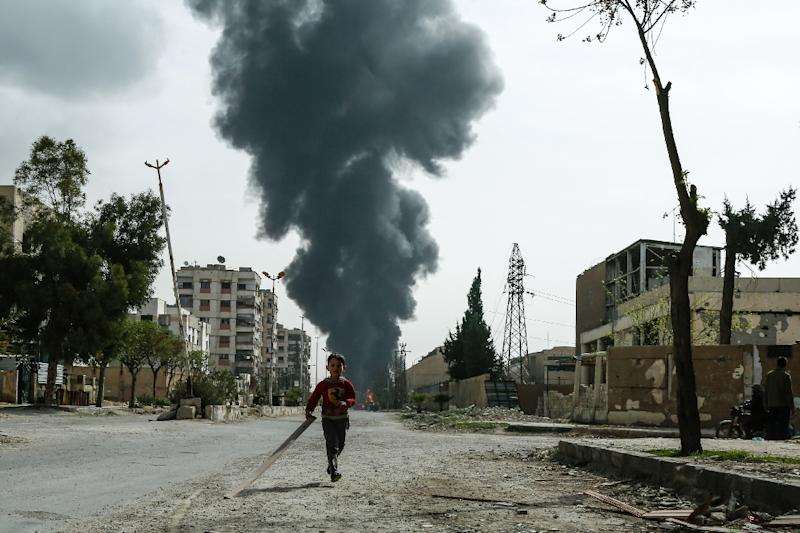 A child runs along a street in front of clouds of smoke following a reported air strike on Douma, the main town of Syria's rebel enclave of Eastern Ghouta, on March 20, 2018 (AFP Photo/HASAN MOHAMED)