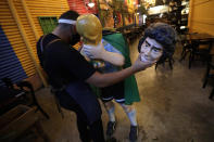 An employee holds the head of a sculpture of late Argentine soccer legend Diego Maradona as he prepares to move it at the Caminito theme bar, in Brasilia, Brazil, Wednesday, Nov. 25, 2020. The Diego Maradona, the Argentine soccer great who was among the best players ever and who led his country to the 1986 World Cup title before later struggling with cocaine use and obesity, died from a heart attack on Wednesday at his home in Buenos Aires. He was 60. (AP Photo/Eraldo Peres)