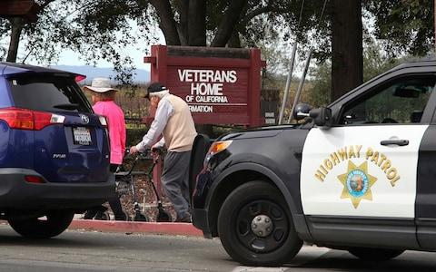 People walk to the information center at the Veterans Home of California in Yountville - Credit: AP