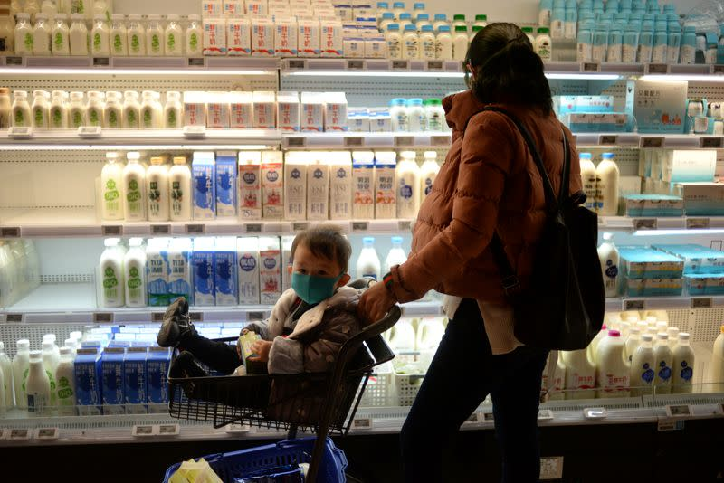 Woman shops as she pushes a trolley with a boy wearing a mask at a supermarket, as the country is hit by an outbreak of the new coronavirus, in Beijing