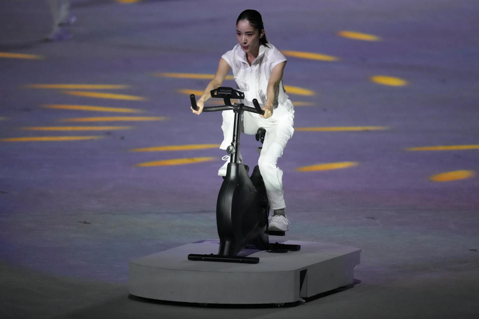 <p>A performer cycles during the opening ceremony in the Olympic Stadium at the 2020 Summer Olympics. (AP Photo/Ashley Landis)</p>