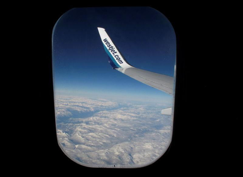 Snow covered mountains are seen under the wing of a WestJet commercial flight on route from Vancouver to Calgary