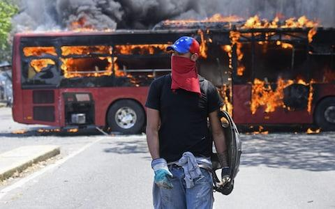 An opposition demonstrator walks near a bus in flames during clashes with soldiers loyal to Maduro - Credit: AFP