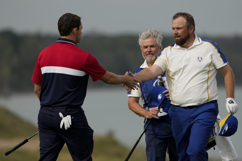 Team USA's Patrick Cantlay shakes hands with Team Europe's Shane Lowry after winning a Ryder Cup singles match at the Whistling Straits Golf Course Sunday, Sept. 26, 2021, in Sheboygan, Wis. (AP Photo/Jeff Roberson)