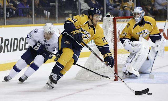 Nashville Predators defenseman Roman Josi (59), of Switzerland, clears the puck out from behind the net ahead of Tampa Bay Lightning center Dana Tyrell (42) in the third period of a preseason NHL hockey game on Tuesday, Sept. 24, 2013, in Nashville, Tenn. At right is goalie Marek Mazanec (39), of the Czech Republic. The Predators won 2-1. (AP Photo/Mark Humphrey)