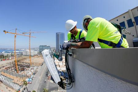 FILE PHOTO: Telecommunications workers Chris Viens and Guy Glover install a new 5G antenna system for AT&T's 5G wireless network in downtown San Diego, California, U.S., April 23, 2019. REUTERS/Mike Blake/File Photo