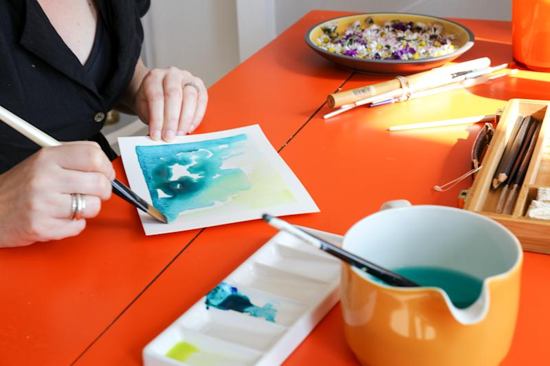 Woman hands making watercolor painting at home