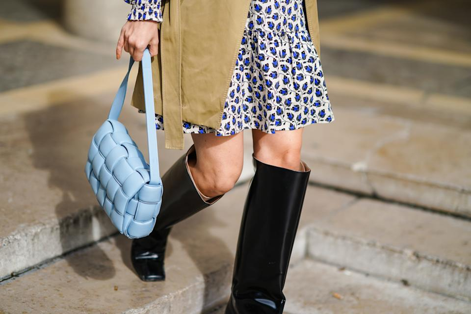 PARIS, FRANCE - OCTOBER 01: Justyna Czerniak wears a beige trench coat, a blue and white floral print pleated dress, a blue quilted Bottega Veneta bag, black leather high boots, outside Chloe, during Paris Fashion Week - Womenswear Spring Summer 2021, on October 01, 2020 in Paris, France. (Photo by Edward Berthelot/Getty Images)