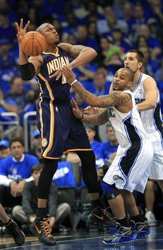 Indiana Pacers' David West, left, loses control of the ball as he is guarded by Orlando Magic's Jameer Nelson, center, and Ryan Anderson, right, during the first half of Game 3 of an NBA first-round playoff basketball series, Wednesday, May 2, 2012, in Orlando, Fla. (AP Photo/John Raoux)
