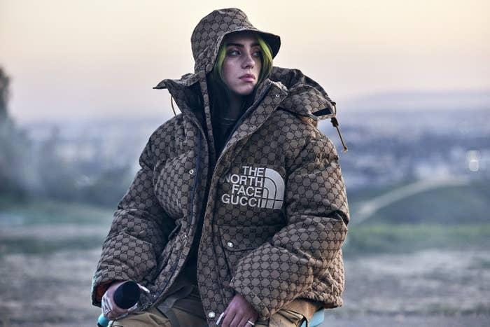 Billie wearing a printed North Face/Gucci puffer jacket with matching bucket hat