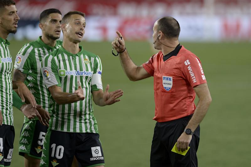 Spanish referee Antonio Mateu Lahoz (R) speaks to Real Betis' Moroccan defender Zouhair Feddal (L), Real Betis' Spanish defender Marc Bartra and Real Betis' Spanish midfielder Sergio Canales (C) during the Spanish League football match between Sevilla FC and Real Betis at the Ramon Sanchez Pizjuan stadium in Seville on June 11, 2020. (Photo by CRISTINA QUICLER / AFP) (Photo by CRISTINA QUICLER/AFP via Getty Images)