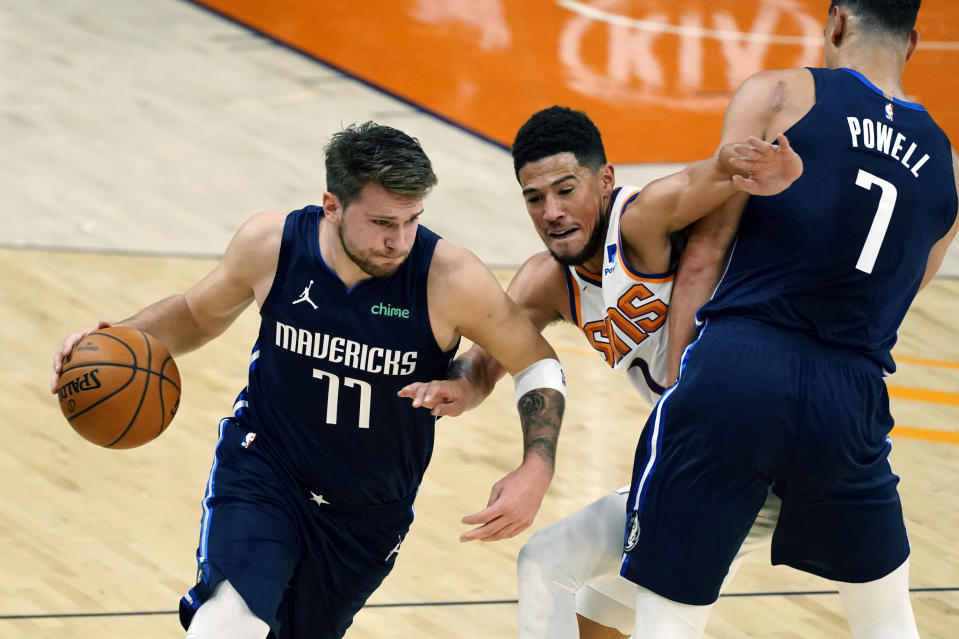 Dallas Mavericks guard Luka Doncic (77) uses the pick by Dwight Powell (7) to drive past Phoenix Suns guard Devin Booker during the first half of an NBA basketball game Wednesday, Dec. 23, 2020, in Phoenix. (AP Photo/Rick Scuteri)