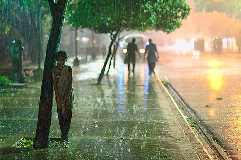It was the evening of May 2009 when Cyclone AILA began battering the coastline of Bangladesh. Three hundred kilometers north, in the capital  city of Dhaka, I found a few street kids frolicking in the rain. One of the girls rested briefly against a tree before disappearing into the  stormy night. <br><br>Camera: Nikon D700 <br><br>Jonathan Munshi, USA <br><br>Runner-up, New Talent portfolio, Diary of a Destination