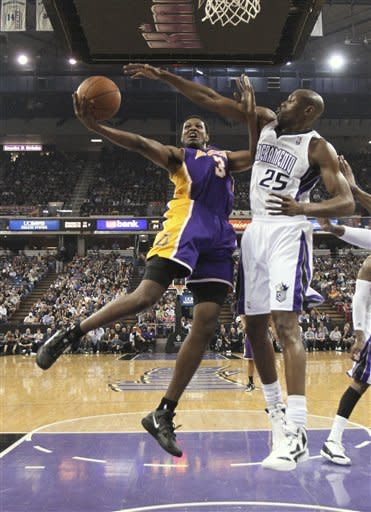 Los Angeles Lakers forward Devin Ebanks, left, goes to the basket against Sacramento Kings forward Travis Outlaw during the first half of an NBA basketball game in Sacramento, Calif., Thursday, April 26, 2012. (AP Photo/Rich Pedroncelli)