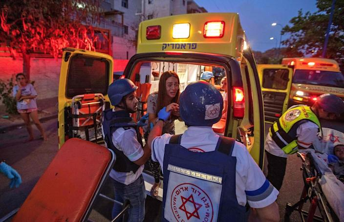 Rescue workers evacuate a woman by ambulance