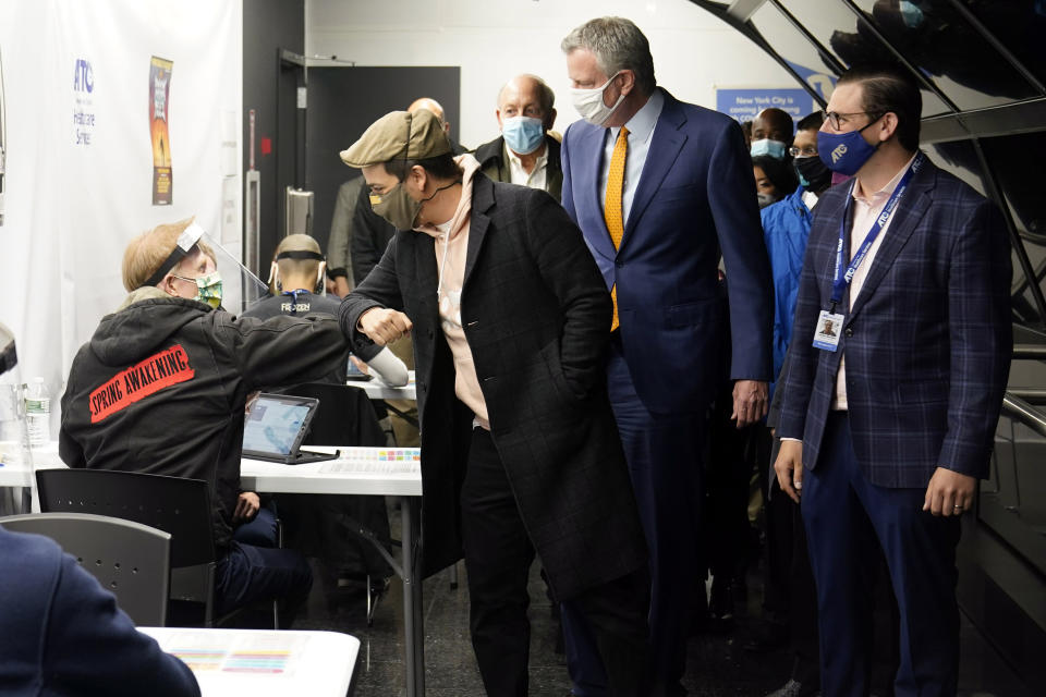 Actor Lin-Manuel Miranda, second left, greets a vaccination site worker, left, as he and New York Mayor Bill de Blasio, third left, tour the grand opening of a Broadway COVID-19 vaccination site intended to jump-start the city's entertainment industry, in New York, Monday, April 12, 2021. (AP Photo/Richard Drew, Pool)