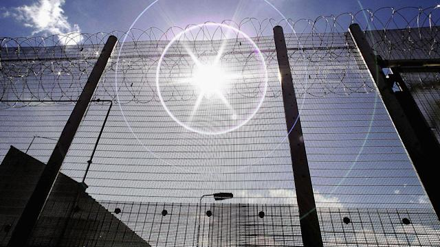 NORWICH, UNITED KINGDOM - AUGUST 25: (EDITORS NOTE: IMAGES EMBARGOED FOR PUBLICATION UNTIL 0001GMT AUGUST 26, 2005; NATURAL LENS FLARE VISIBLE IN IMAGE) The sun shines through high security fencing surrounding Norwich Prison on August 25, 2005 in Norwich, England. A Chief Inspector of Prisons report on Norwich Prison says healthcare accommodation was among the worst seen, as prisoners suffered from unscreened toilets, little natural light, poor suicide prevention, inadequate education and training for long-term prisoners. (Photo by Peter Macdiarmid/Getty Images) Photographer: Peter Macdiarmid/Getty Images Europe