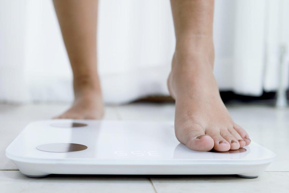 A person steps onto bathroom scales, their ankles and feet visible.