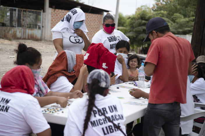 """Women who say they are part of a female-led, self-defense group, some wearing T-shirts with a message that reads in Spanish: """"For a free Michoacan,"""" play board games at a check-point they set up to protect the entrance of their town of El Terrero, in Michoacan state, Mexico, Thursday, Jan. 14, 2021. Many of the women vigilantes in the hamlet of El Terrero have lost sons, brothers or fathers in the fighting. (AP Photo/Armando Solis)"""