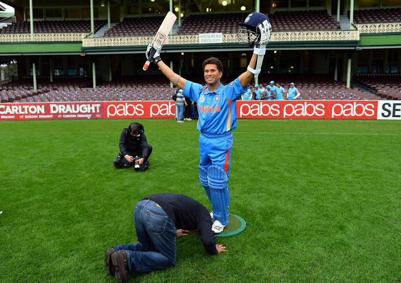 A Indian cricket fan kisses the shoe of a wax figure of India's legendary cricket star Sachin Tendulkar, at the Sydney Cricket Ground in Sydney on April 20, 2013. The new wax figure of Tendulkar will be placed in the sports zone of Madame Tussauds in Sydney.  AFP PHOTO / Saeed Khan