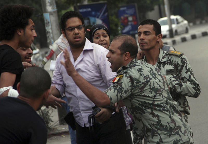 An Egyptian Army officer argues with protesters demonstrating in front of the Saudi Embassy in Cairo, Egypt to demand the release of an Egyptian human rights lawyer detained in Saudi Arabia for allegedly insulting the kingdom's monarch, Saturday, April 28, 2012. Saudi Arabia said Saturday that it has closed embassy in Cairo because of protests over a detained Egyptian. (AP Photo/Ahmed Gomaa)