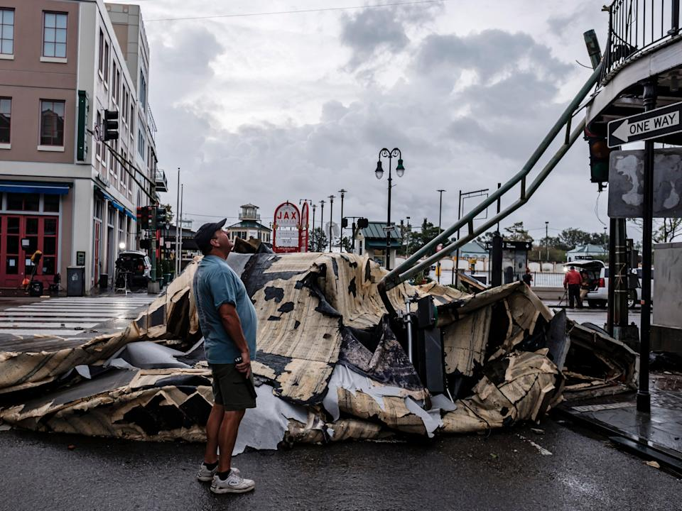 A man looks up next to a chunk of roof that ripped off a building the French Quarter due to Hurricane Ida in New Orleans, Louisiana (EPA)