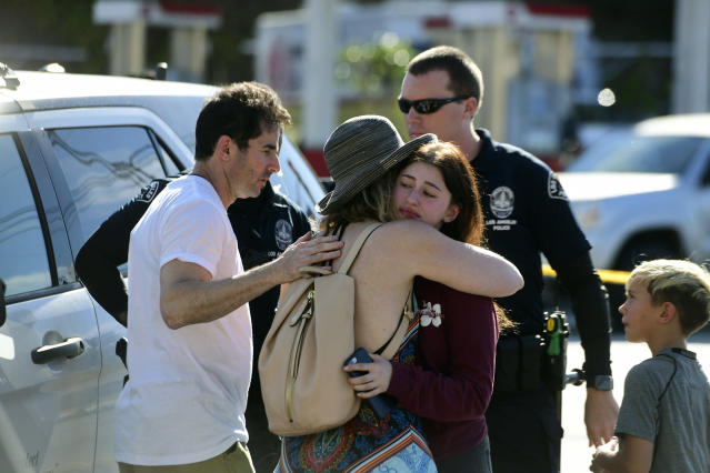 <p>a Trader Joes employee hugs her loved ones just outside the store where a man held employees hostage and killed one woman in Silverlake, Calif. on Saturday, July 21, 2018. (Photo: Christian Monterosa via AP) </p>