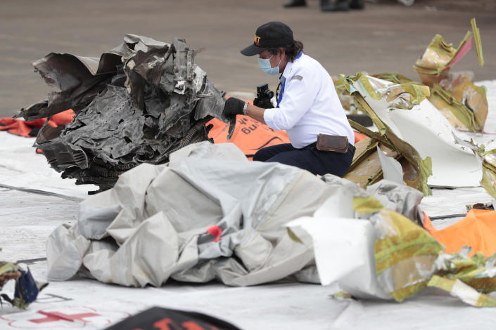 An investigator of the National Transportation Safety Committee inspects parts of aircraft's debris recovered from the Java Sea where a Sriwijaya Air passenger jet crashed, at Tanjung Priok Port, Tuesday, Jan. 12, 2021. Indonesian navy divers were searching through plane debris and seabed mud Tuesday looking for the black boxes of the Sriwijaya Air jet that nosedived into the Java Sea over the weekend with 62 people aboard. (AP Photo/Dita Alangkara)