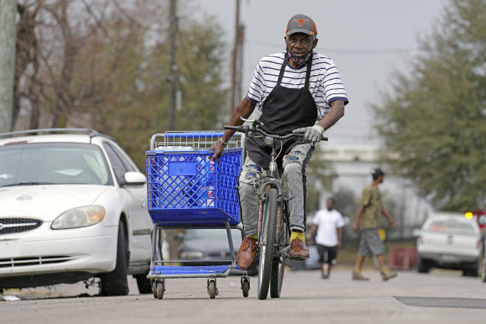 Mark Johnson pulls a shopping cart with cases of donated water back to his home, which was without running water after a recent winter storm, Friday, Feb. 26, 2021, in Houston. Local officials, including Houston Mayor Sylvester Turner, say they have focused their efforts during the different disasters on helping the underserved and under-resourced but that their work is far from complete. (AP Photo/David J. Phillip)
