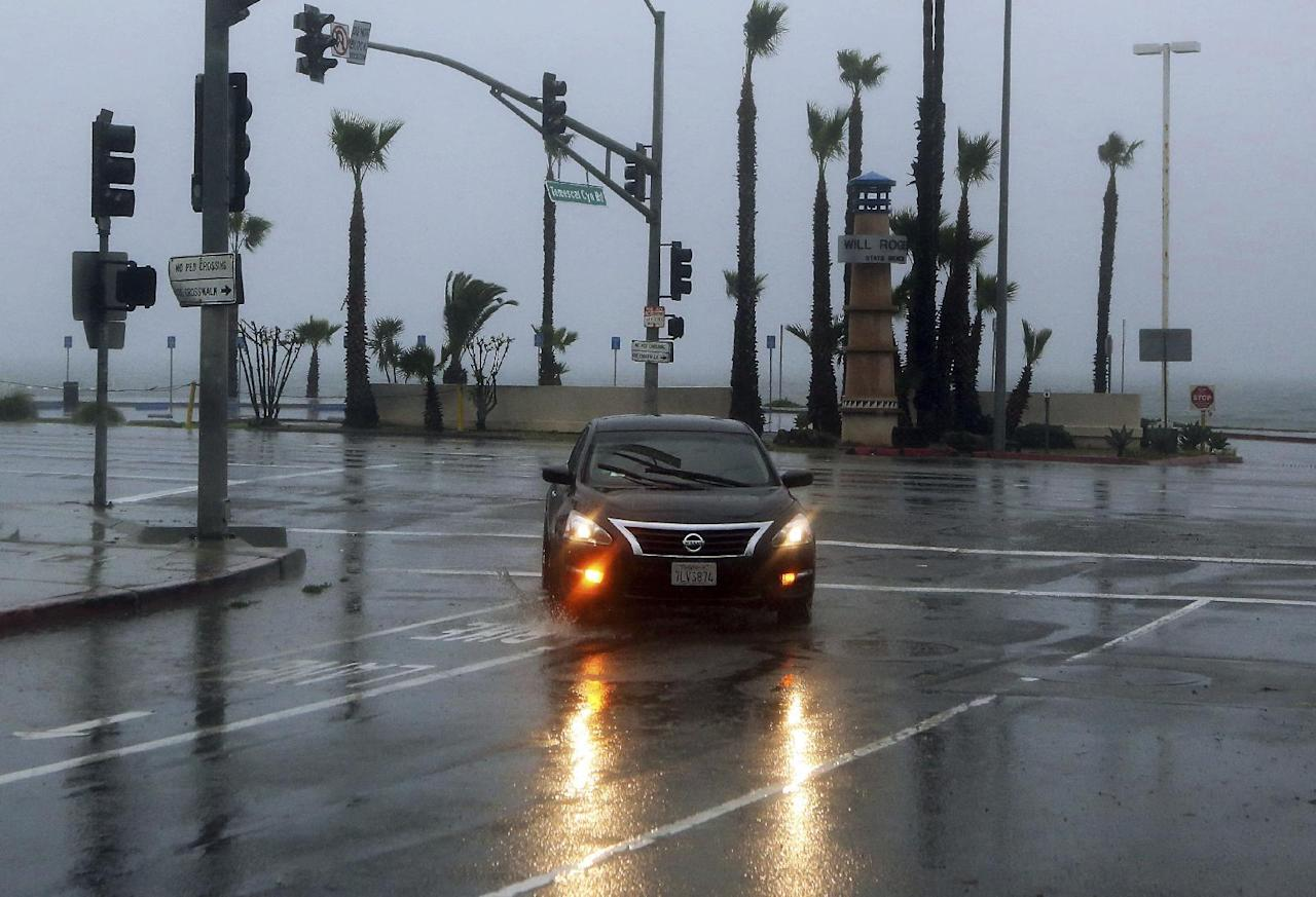 A car turns off Pacific Coast Highway during a downpour in the Pacific Palisades area of Los Angeles, Friday morning, Jan. 20, 2017. The second in a trio of storms has brought rain, heavy at times, over a wide area of California. The National Weather Service has issued a flood advisory for San Luis Obispo County as moderate to heavy rain falls on the Central Coast.(AP Photo/Reed Saxon)
