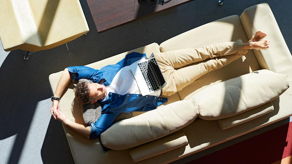 Full length shot from above of a closed eyes middle aged man lying on sofa and relaxing at home.