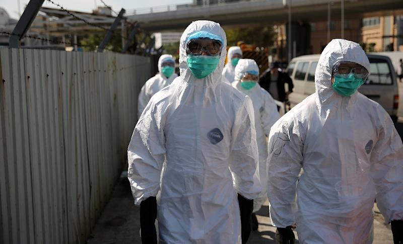 Workers with protective gear walk into a restricted area where chickens are being culled in Hong Kong on December 31, 2014, after the deadly H7N9 virus was discovered in poultry imported from China (AFP Photo/Isaac Lawrence)