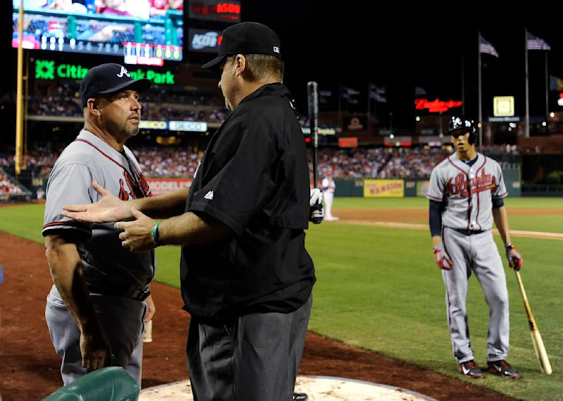 Atlanta Braves manager Fredi Gonzalez, left, talks to third base umpire Gary Cederstrom after a home run hit by B.J. Upton was reviewed and ruled a double in the fourth inning of a baseball game against the Philadelphia Phillies on Sunday, Aug. 4, 2013, in Philadelphia. (AP Photo/Michael Perez)