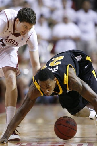 VCU's Treveon Graham (21), right and Temple's Jake O'Brien (22) chase a loose ball in the first half of an NCAA College basketball game, Sunday, March 10, 2013, in Philadelphia. (AP Photo/H. Rumph Jr)