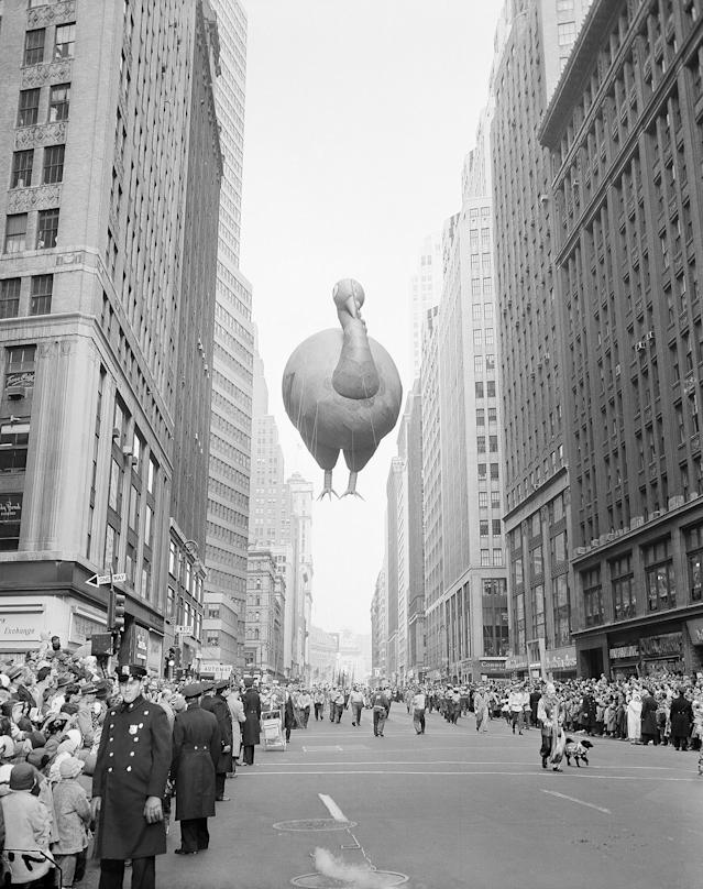 <p>A giant turkey float squeezes between buildings as the 31st annual Macy's Thanksgiving Day Parade moves down Broadway near 37th Street in New York, Nov. 28, 1957. (Photo: John Lindsay/AP) </p>