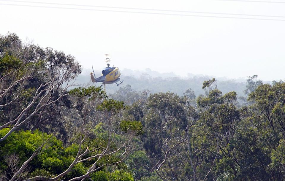 A water bomber helicopter returns to fill its tank in the Blackwater creek of Deepwater National Park. Image: Getty