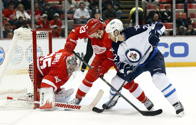 Detroit Red Wings goalie Jimmy Howard (35) stops Winnipeg Jets right wing Chris Thorburn, right. shot as Brian Lashoff (23) defends in the first period of an NHL hockey game in Detroit, Tuesday, Nov. 12, 2013. (AP Photo/Paul Sancya)