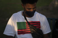 """Kilo Martin, 29, wears a T-shirt printed with an American flag in the pan-African colors Monday, Oct. 19, 2020, in Santa Monica, Calif. """"I'm voting for Biden,"""" said the writer. """"I'm afraid of the other option, very afraid of the other option if they get chosen."""" (AP Photo/Jae C. Hong)"""